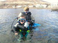 Helping a daycourse student into equipment in the water