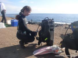 A Junior PADI diver prepares and checks her own equipment before a dive in Gran Canaria
